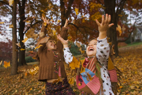 Children playing with autumn leaves